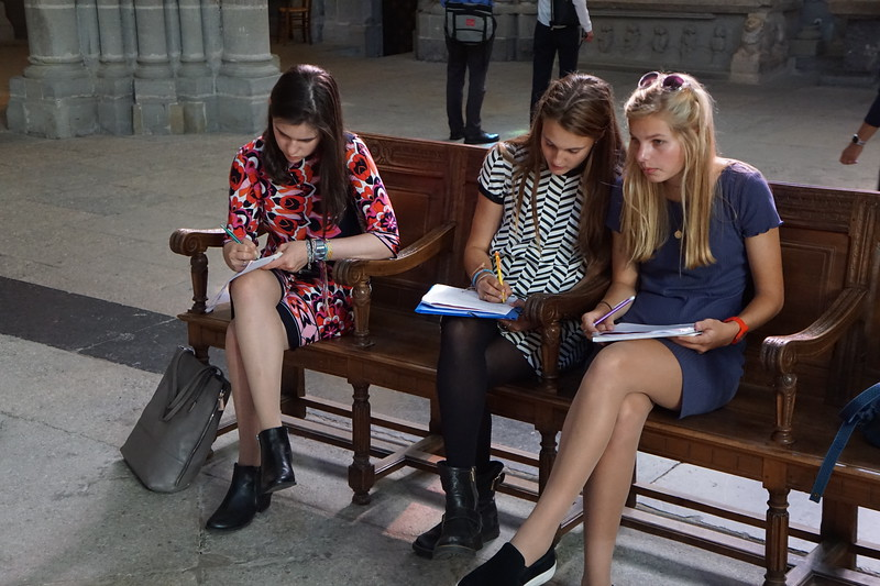 Aisling, Kate, and Maddie working on their assignment in the Lausanne Cathedral
