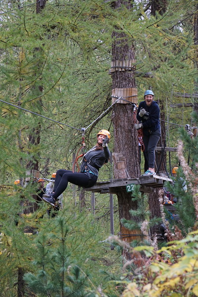 Nicole on the zip line while Mary Neely is laughing behind