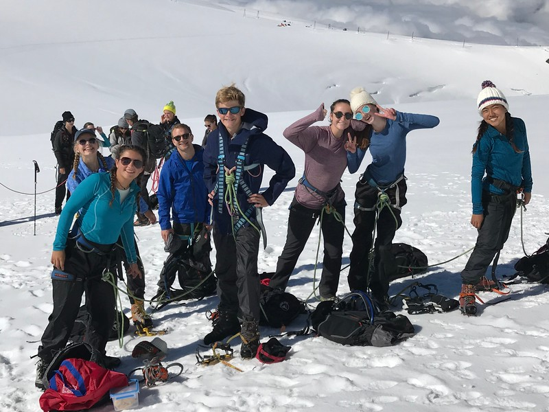 Putting on crampons at the halfway point of the Breithorn climb (Maddie, Nicole, Mr. Taylor, Ryan, Mary Neely, Charlotte, and Alana)