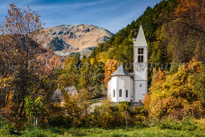 A rural Swiss church with fall foliage color in the Canton of Graubünden,Switzerland, Europe.