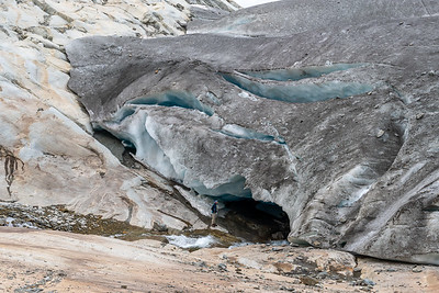 A hiker investigates the hole formed by a stream rushing under the edge of the glacier.