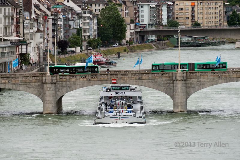 """Heavily laden tanker passing under the Mittlere Bridge heading upstream  against a strong current, Basel, Switzerland (best at larger size).  Two trams are passing over the bridge above.<br /> <br /> The Rhine River was in flood and there wasn't a lot of clearance under the bridge.  From this angle it looks like the boat is about to collide with the bridge.  To see what happened, click here:  <a href=""""http://goo.gl/xGmwRe"""">http://goo.gl/xGmwRe</a><br /> <br /> 8/10/13  <a href=""""http://www.allenfotowild.com"""">http://www.allenfotowild.com</a>"""
