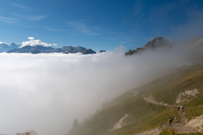 The trail follows the contour, and finally pops above the undercast clouds.