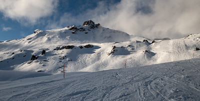 Skiers' carved turns, the morning after powder at Flumserberg.