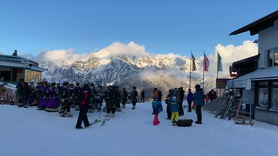 A marching band, in costume, plays pop tunes near the base of the gondola at Flumserberg.