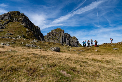 The group pauses at the pass on the south slope of Gandstock, with its peak behind.
