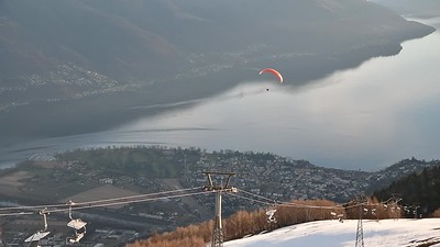 Paragliders taking off from the peak above Locano