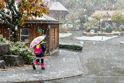 Child walking to school on a snowy day in Flueli-Ranft, Switzerland.
