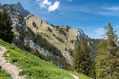 Andy descends through the alpine meadows below the peaks of Pilatus.
