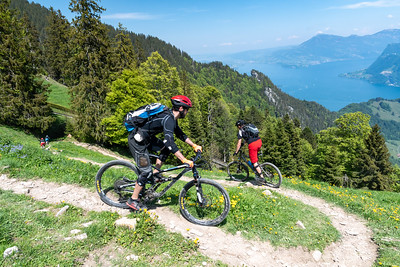 Mountain bikers descend Pilatus while sailboats ply Lake Luzern and a paraglider is visible as a red speck below and right of Rigi's summit.