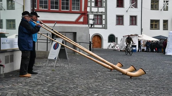 Three men play the alphorn, in St Gallen, Switzerland.