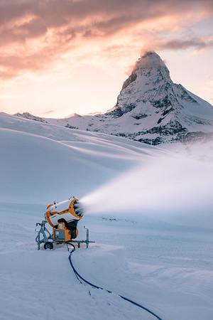 A snow cannon near the Matterhorn at sunset