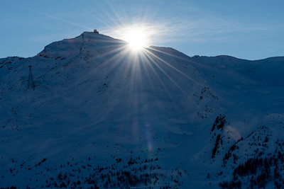 The sun appears above the ridgeline, from Sunnegga, above Zermatt.