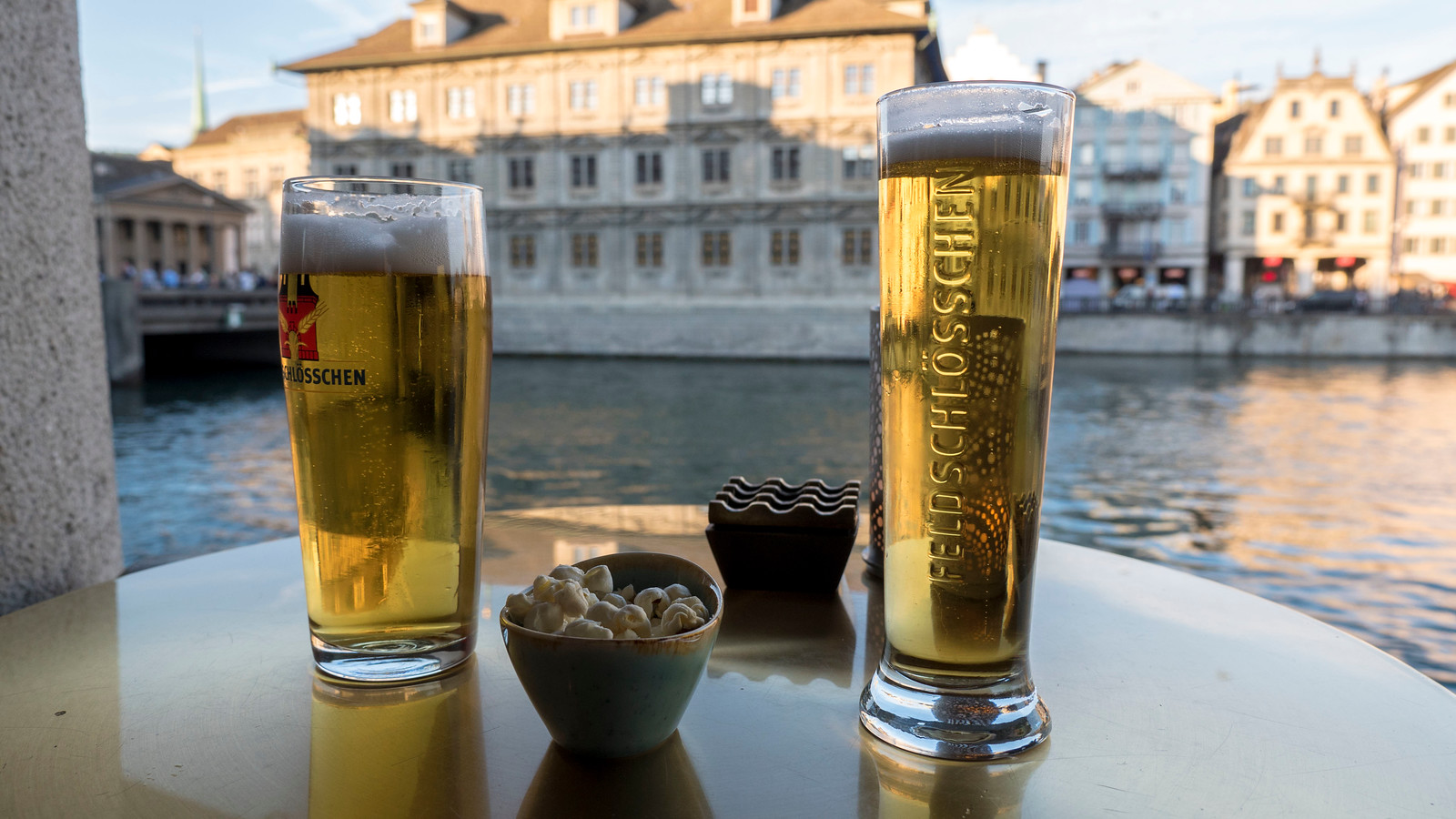 Beer on the terrace with river views at the Hotel Storchen Zurich.