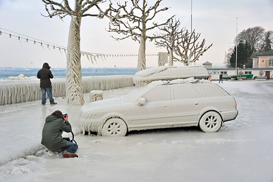 Photographer photographing a car frozen in ice in Versoix, Switzerland, by Lake Geneva