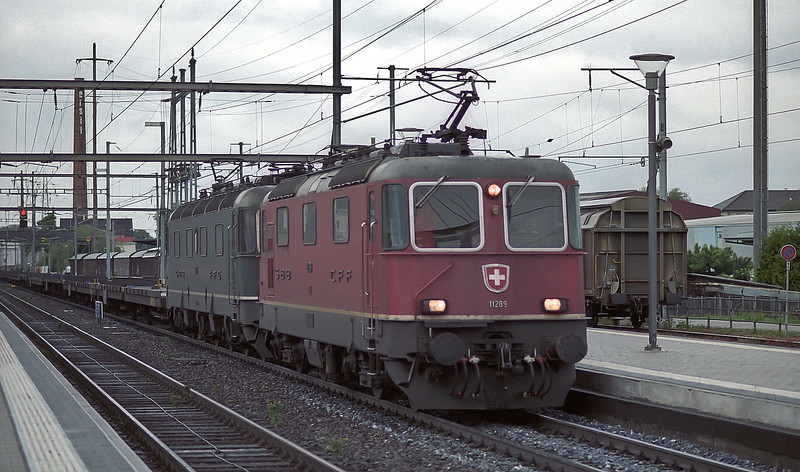 With a train of empty flats behind them Re4/4ii 11289 and Re6/6 11675 'Gelterkinden' pass Pratteln on 16 May 2007