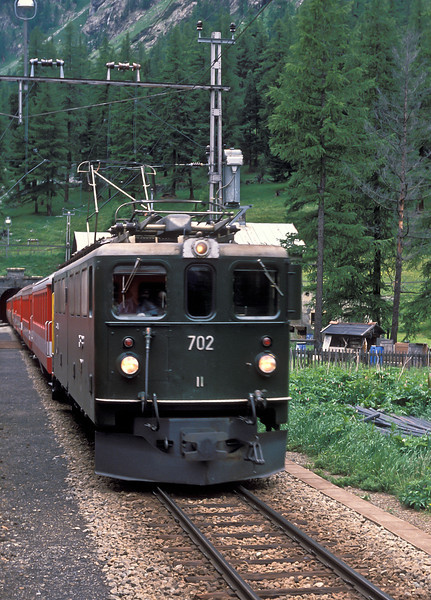 RhB Ge6/6 II 702 'Curia' is still in original body condition and green livery bursting out of the Albula Tunnel on 4 July 1988 with train 567, the 'Glacier Express'
