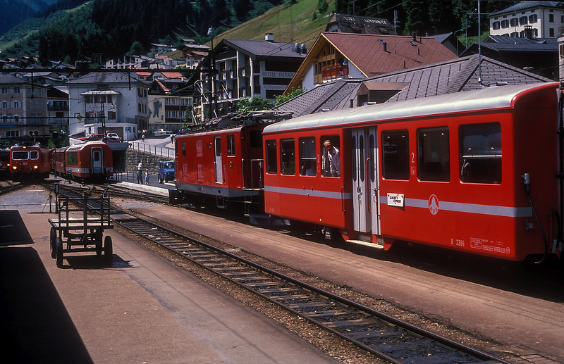It's the rush hour at Disentis/Muster on 6 July 1988 as the Glacier Express puts on a show. RhB Ge4/4ii 614 'Schiers' has brought in the service and has now uncoupled (far left) as FO HGe4/4 37 waits in the platform with the second portion of train 51, the 1358 to Zermatt. Furka Oberalp HGe4/4ii 102 'Altdorf' is running back onto train 538 from St. Moritz and Chur which will now become the first portion of train 51