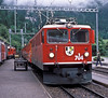 RhB Ge6/6 II 704 'Davos' pulls into Filisur on 4 July 1988. As is usual on this heavily worked single track line the passing station is busy with a freight waiting to go to Samedan and the railcar for Davos