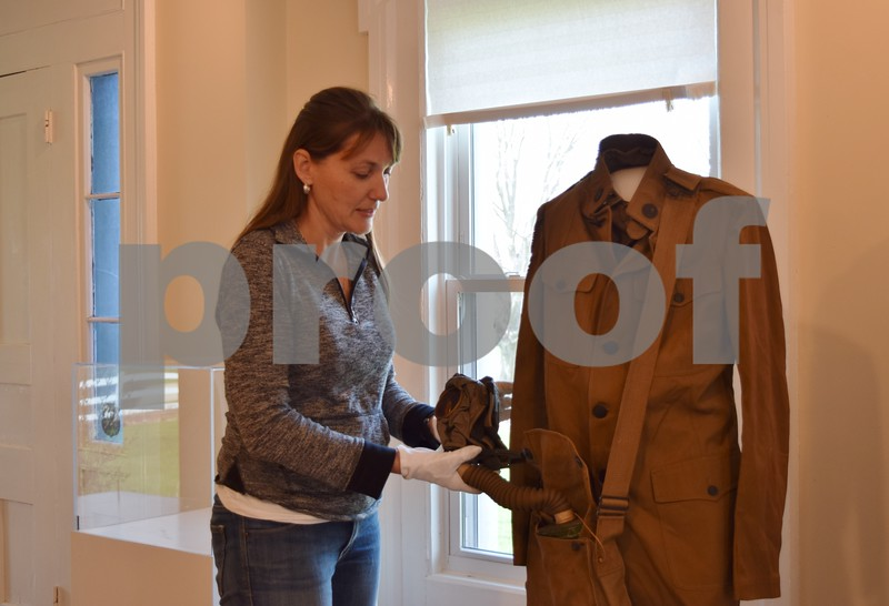 """Michelle Donahoe, the executive director at the Sycamore History Museum, 1730 N. Main St. in Sycamore, adjusts the gas mask on a World War I uniform. The museum's new exhibit, """"Adventures To and From Sycamore,"""" tells the stories of people from Sycamore, the interesting places they have traveled and how they either came to live in or came to leave Sycamore. The exhibit will have four themes: education, immigration, exploration and military."""