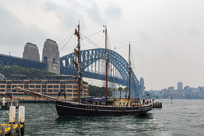 The Sydney Harbor bridge and a vintage gondola, boat or ship in the harbor on a rather cloudy day in Sydney New South Wales, Australia