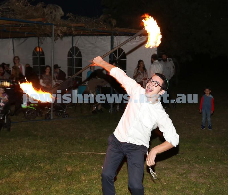 Pizza In The Hut Succot Party at Barracluff Park in Bondi. Mendel Slavin twirls a fire stick.
