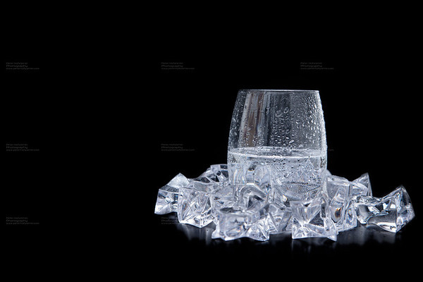 glass of water with ice and bubbles on black background