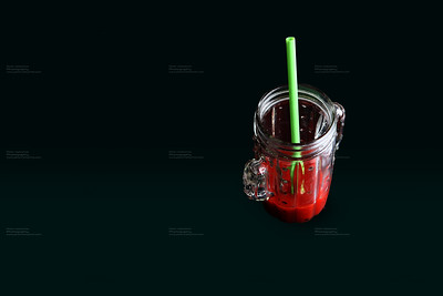glass of tomate juice in with straw withblack bckground
