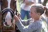 A young girl ties her lead before a big ride.