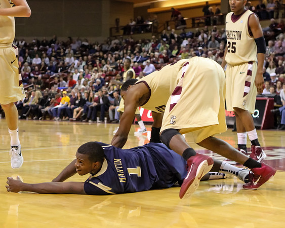 Kelvin Martin (1, CSU) watches the ball go out of bounds from floor-level as Antwaine Wiggins (30, College of Charleston) looms over him. When the dust settled, the Cougars came out on top of the Bucs, 70-68. December 17, 2011