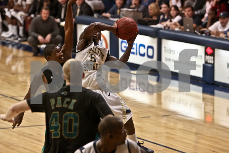 Saah Nimley (5, CSU) muscles his way past Kierre Greenwood (55, CCU) to get a shot off. Coastal Carolina won the game in over-time, 80-77. January 7, 2011