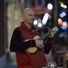 Photo by Aaron Beckman  <br /> <br /> Chad Barnhill, owner of Midwest Music in Norfolk, plays his ukulele Tuesday night on the sidewalk out in front of Midwest Music during the Downtown Riverpoint Christmas Festival.