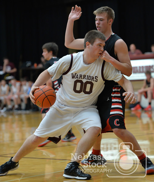 Photo by Aaron Beckman  <br /> <br /> Neligh's Ben Lingenfelter takes a shot to the face while driving to the basket against Creighton's Beau Schindler Friday night in Neligh.