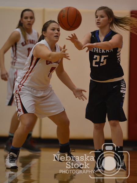 Photo by Aaron Beckman  <br /> <br /> Lutheran High's Jacey Kant passes the ball around Norfolk Catholic's Maddie Love Thursday night in Norfolk.