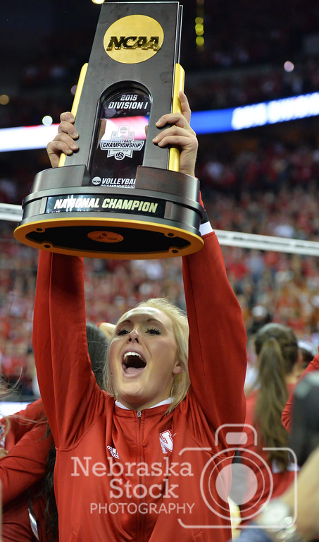 Photo by Aaron Beckman    Nebraska's Olivia Boender holds up the NCAA Volleyball Trophy Saturday night after the Huskers defeated Texas in 3 sets.