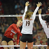 Photo by Aaron Beckman  <br /> <br /> Husker's Amber Rolfzen attempts to spike a ball between a couple of Texas's defenders Saturday night in Omaha.