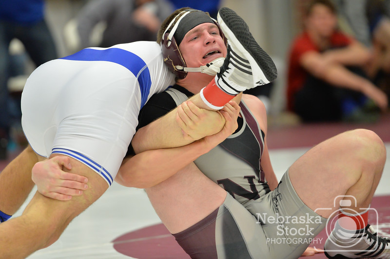 Aaron Beckman / Daily News  <br /> <br /> Norfolk's Josh Kohl is wrapped up by Creighton Prep's Derrick Hobbs in the 160 lb championship match Saturday in Norfolk. Kohl was defeated by Hobbs.
