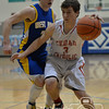 Photo by Aaron Beckman  <br /> <br /> Hartington CC's Jared Wiebelhaus dribbles around West Holt's Sawyer Williams Monday night in Pierce during the Boys C2-4 District finals.