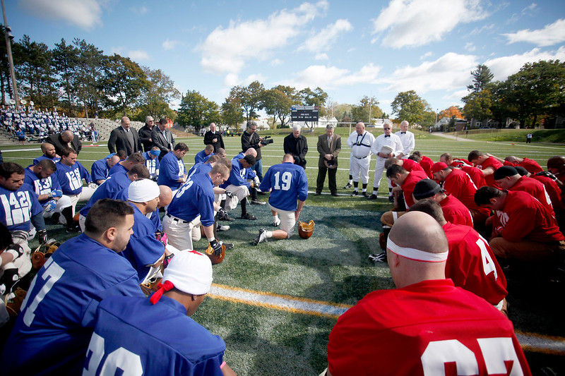 SENTINEL & ENTERPRISE / CONNOR GLEASON<br /> Members of the Fitchburg High School Redskins and the Leominster Blue and White Warriors meet for a prayer before the 1933 recreation game between at Doyle Field in Leominster Saturday afternoon. The game recreated the historic 1933 Thanksgiving Day game between the two undefeated teams.The Fitchburg Redskins defeated the Leominster Blue and White Warriors, 15-14.