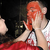 SENTINEL & ENTERPRISE / JONATHAN PHILLIPS<br /> Fitchburg High School senior Joe olomeo, 17, has his face painted red by junior Sarah Wilson, 16, during the tailgate party and pep rally at the school, Tuesday night.