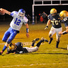 NASHOBA PUBLISHING / BRETT CRAWFORD<br /> Lunenburg quarterback Greg Abare avoids a tackle by St. Bernard's Aaron Robichaud as St. Bernard's Brendan Kelley (76) and Garrett Brissette (54) run on during Wednesday night's Thanksgiving Eve game at the Bernardian Bowl in Fitchburg. Lunenburg won 36-8.