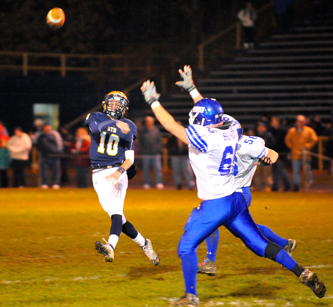 NASHOBA PUBLISHING / BRETT CRAWFORD<br /> St. Bernard's quarterback Justin Valliere throws the ball as Lunenburg's Matt Benoit puts up his arms to block during Wednesday night's Thanksgiving Eve game at the Bernardian Bowl in Fitchburg. Lunenburg won 36-8.