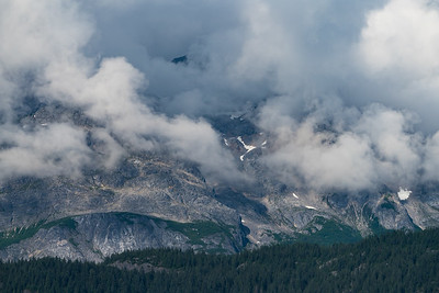 Low clouds add drama to the steep rocky slopes of mountains in Glacier Bay, Alaska.
