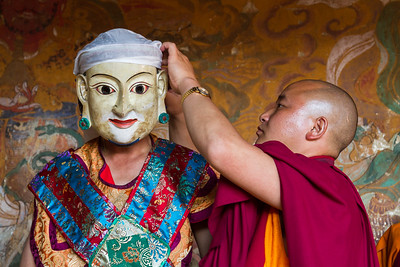 A monk helps another get dressed for dance at festival, Bhutan.