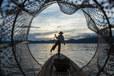 Fisherman paddles on Inle Lake, Myanmar.
