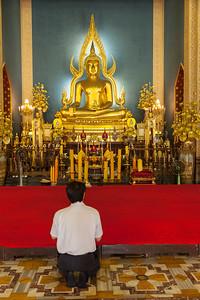Man Praying at Buddhist Altar.