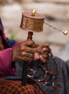 Bhutanese woman prays with prayer wheel and beads.