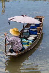 Woman Food Vendor paddling boat.