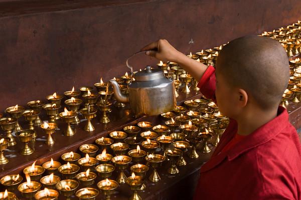 A Bhutanese nun fills butter lamps, Thimpu.