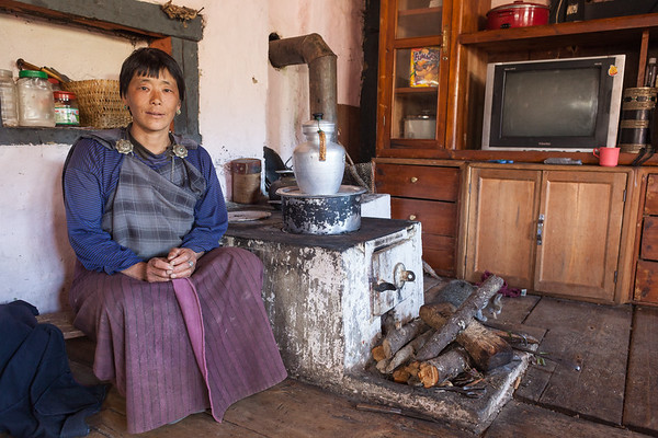 Portrait of woman by her woodstove, Bhutan.